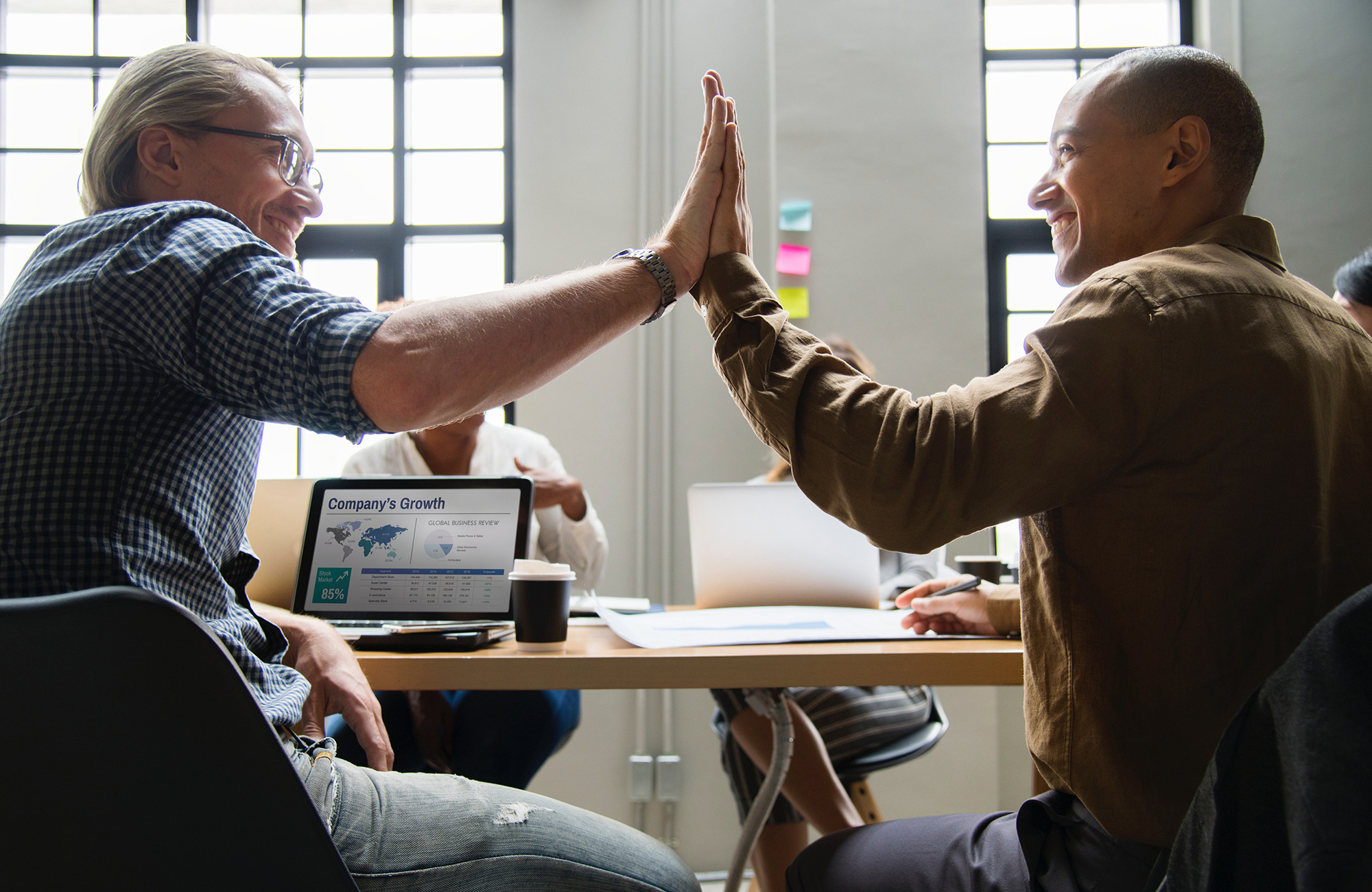 Two people high-fiving at office meeting
